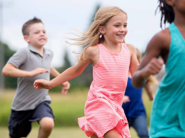 Child monitoring asthma while running through a field.