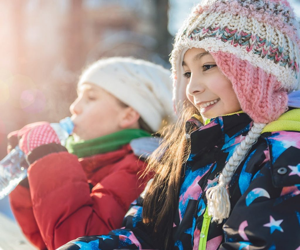 two children playing outside during winter