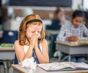 a girl sitting at a school desk sneezing because she isn't in an asthma friendly school