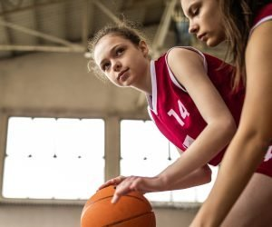 Two girls in school uniform playing basketball
