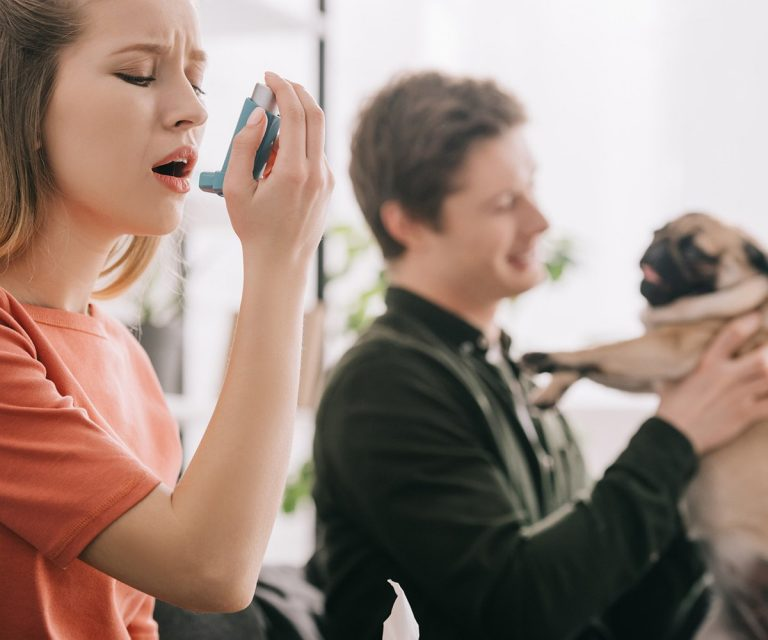 girl using an asthma inhaler for asthma triggers