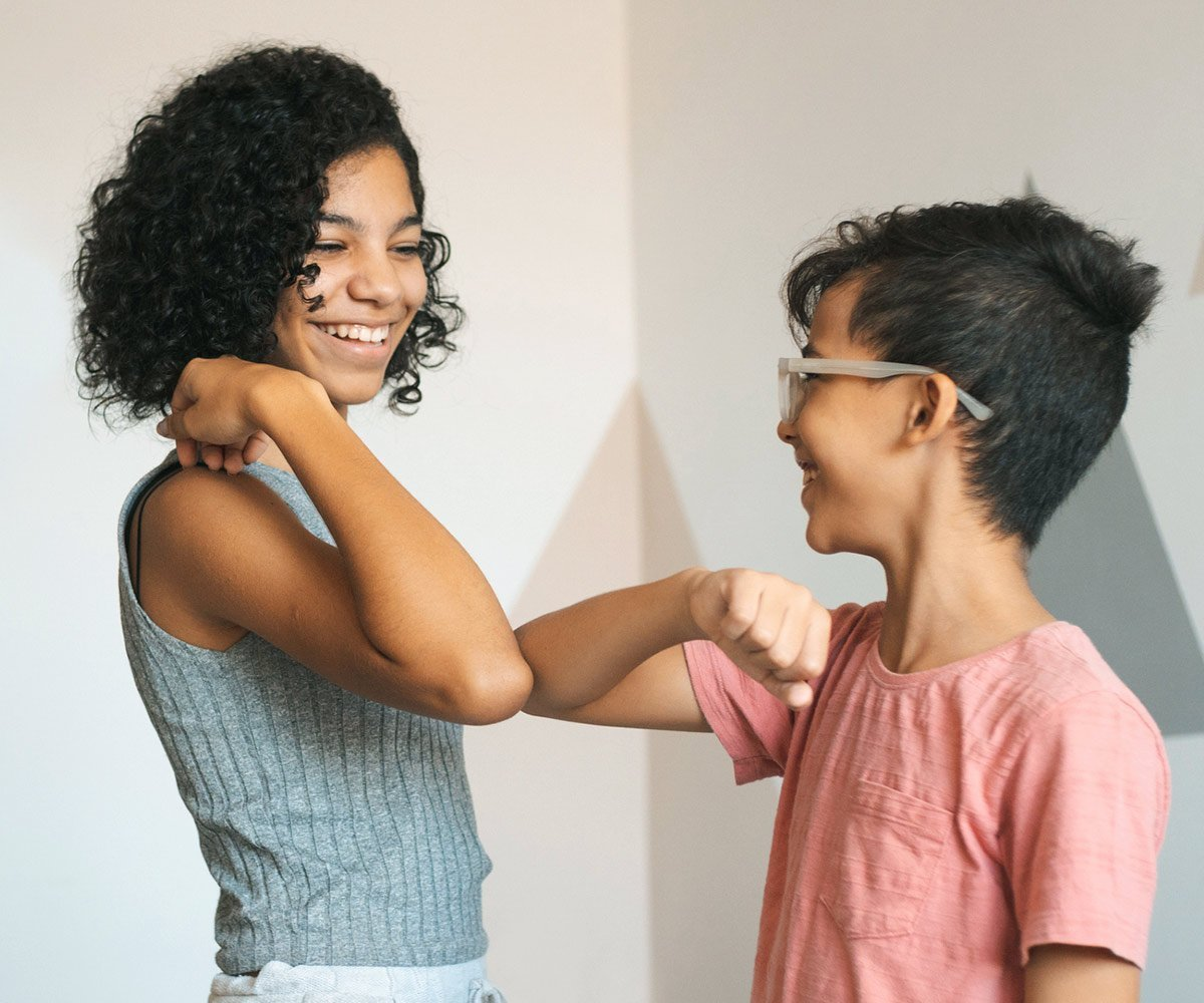 Boy and girl touching elbows as a greeting to prevent spreading sickness