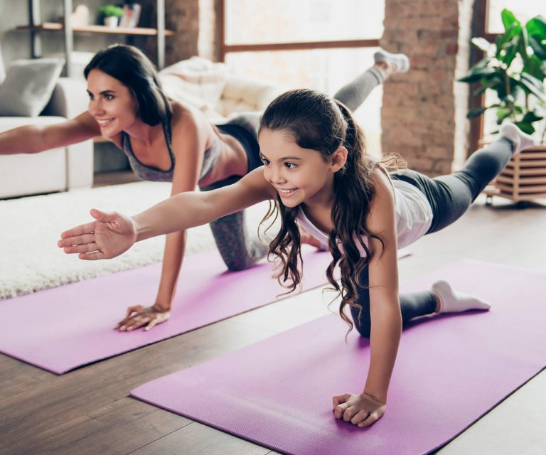 girl and mother doing yoga in living room