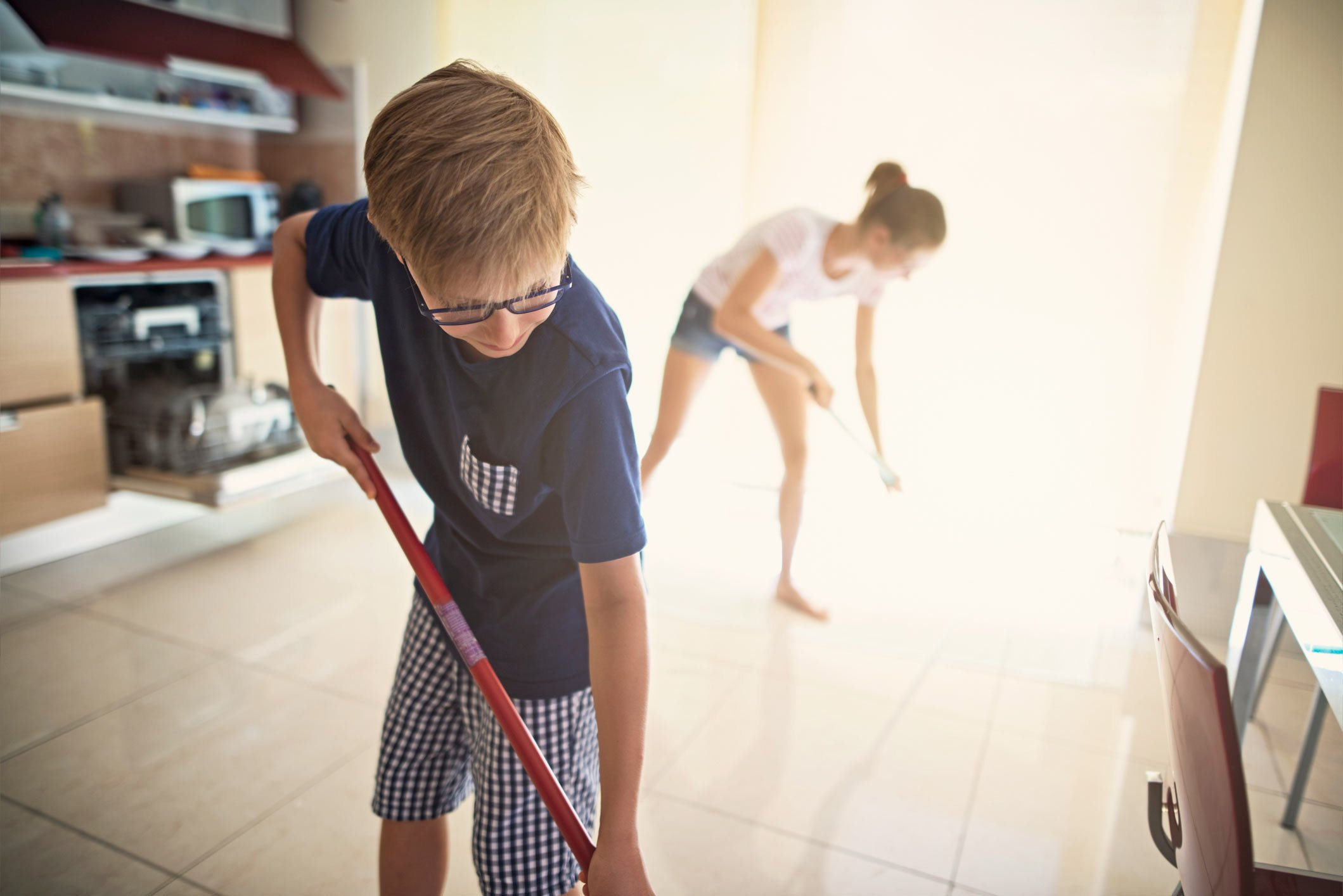 brother and sister mopping floors at home