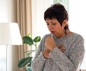 Adult woman in her home standing and coughing
