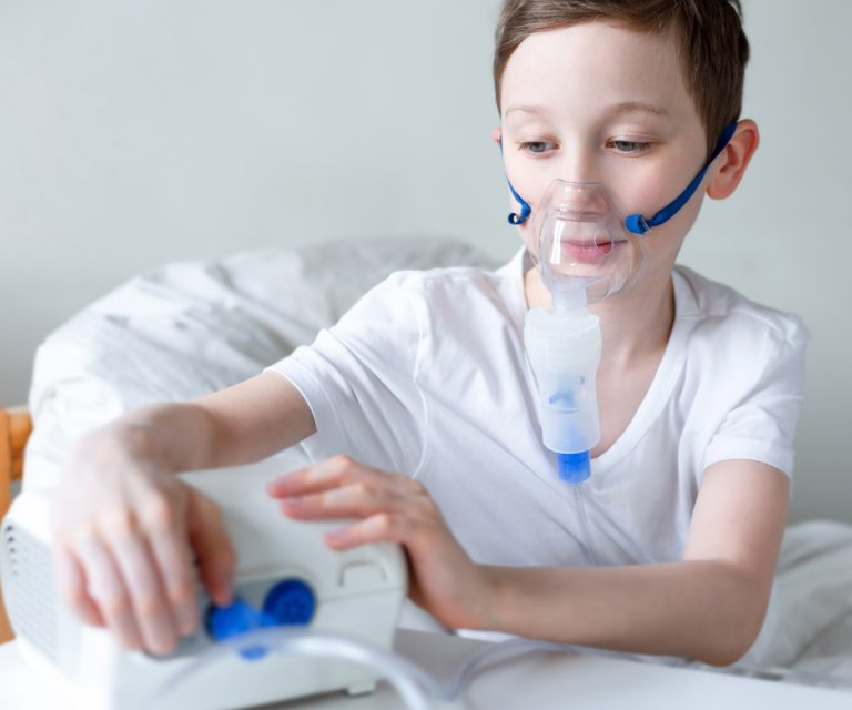 Young boy using his nebulizer while in bed
