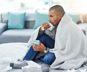 man at home, coughing and sneezing, covered in blanket