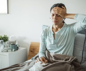 woman in bed, holding hand over forehead feeling for fever