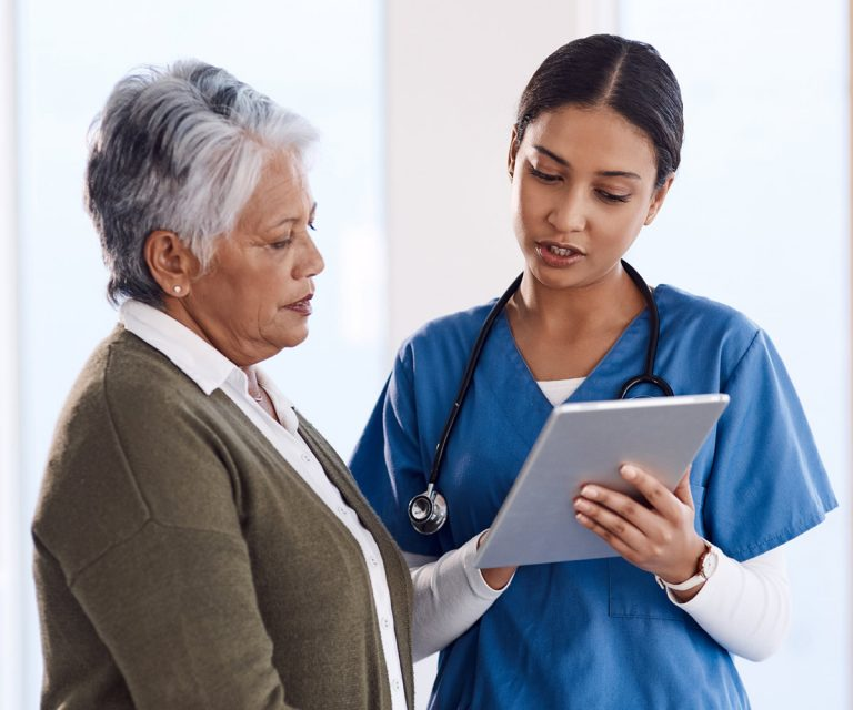Female doctor explains stats to elderly patient using an ipad.