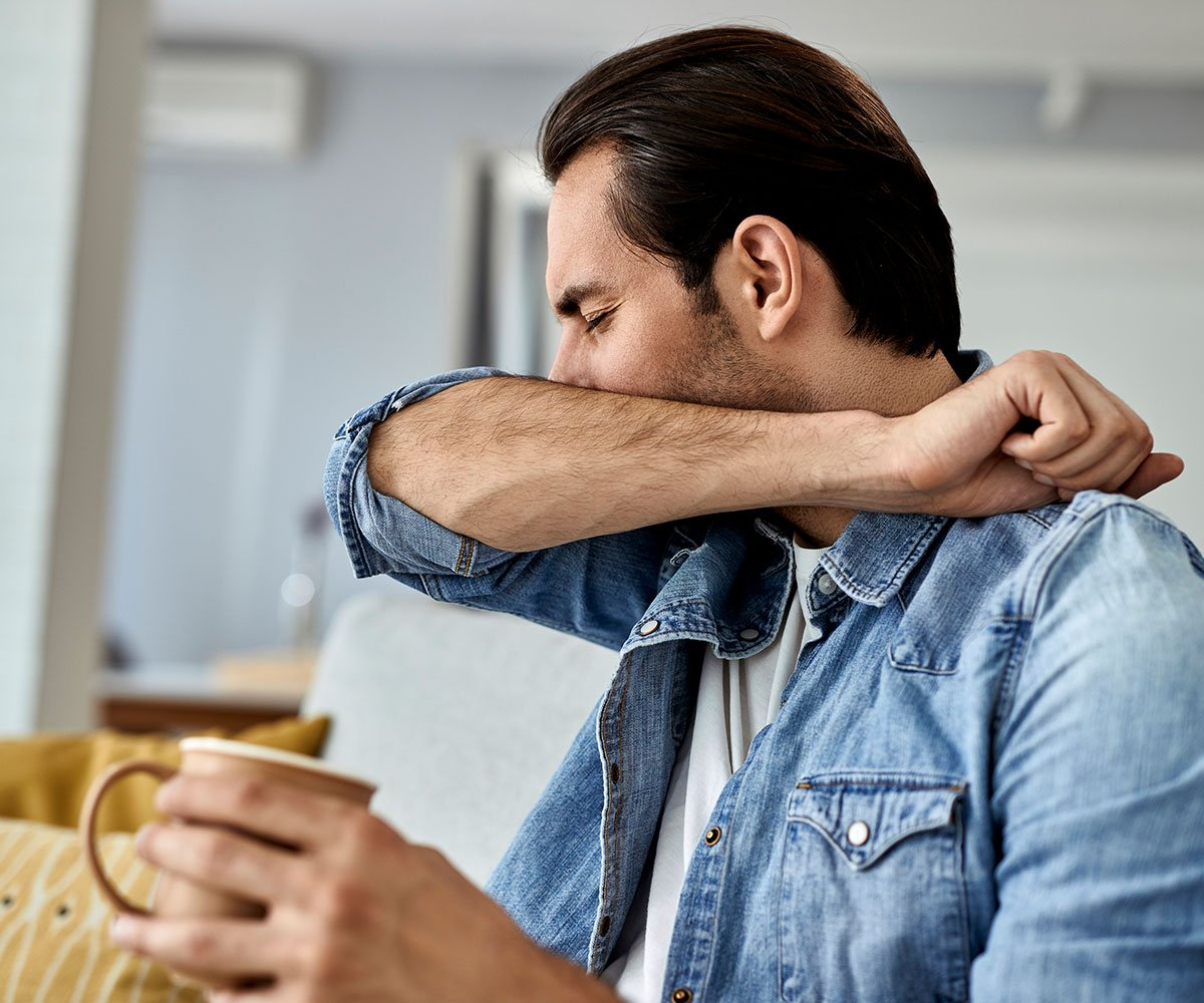 Man sitting at home on couch with tea coughing into arm