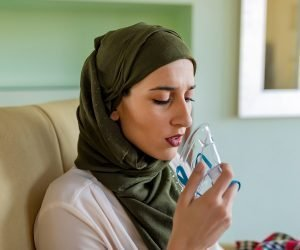 woman wearing green hijab at home on couch using nebulizer
