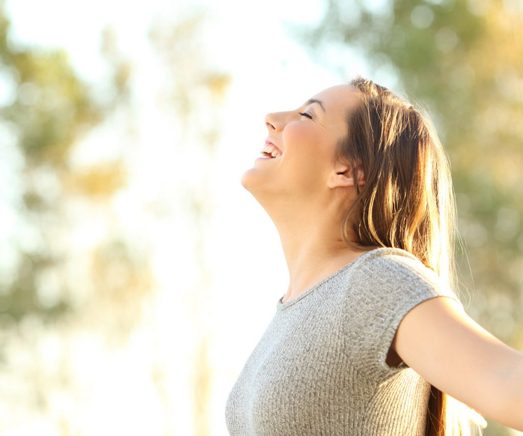 Woman with eyes closed and arms outstretched stands in the sun smiling