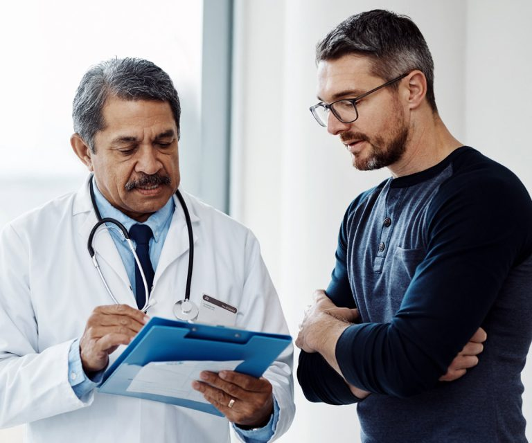 Adult caucasian male reviewing notes with Asian doctor in office