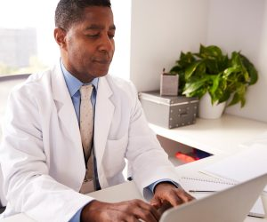 Male doctor sitting at desk using laptop