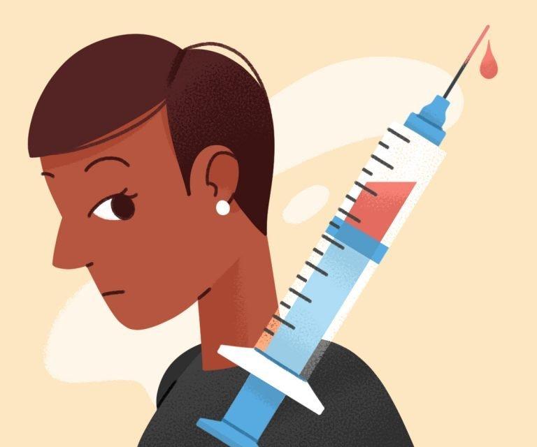 woman looks at syringe