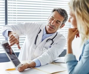 doctor reviews medical information with his patient